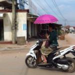 Většina žen a dívek jezdí na motorce s deštníkem (proti slunci)
